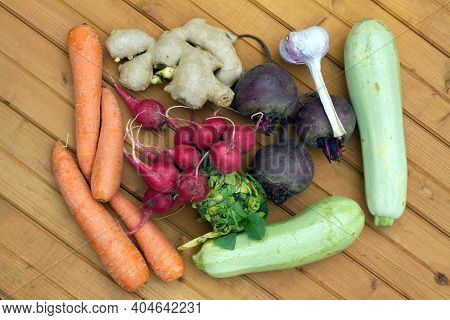 Still Life With Crop Of Ripe Beetroots, Carrots, Ginger, Radishes, Squash And Garlic On Brown Wooden