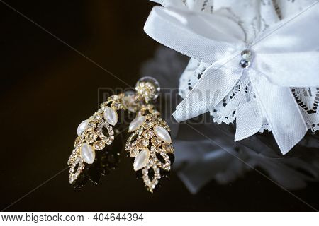Luxury Earrings Made Of Crystals And Rhinestones And The Bride's Garter On The Glass Table. Wedding