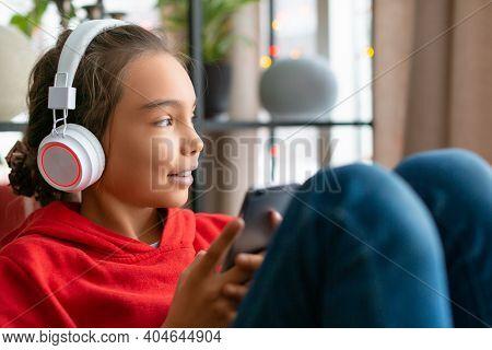 Teenager Girl Listening To The Music Via Headphones Via Online App In Mobile Phone. Modern Technolog