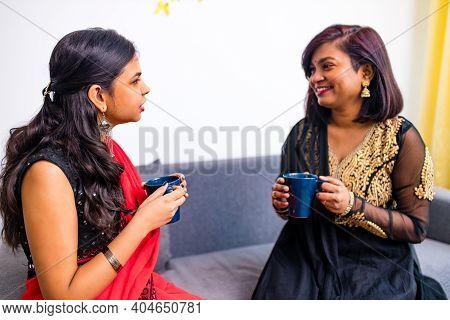 Two Indian Women Enjoying Masala Tea Together In Living Room