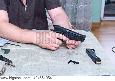 Assembled Traumatic Pistol. Gun In Hand. Gun And Parts. View From Above.