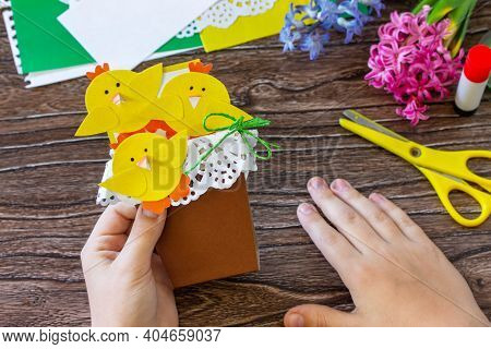 Child Holds A Gift Postcard Happy Easter Chickens Toy On A Wooden Table. Handmade. Project Of Childr