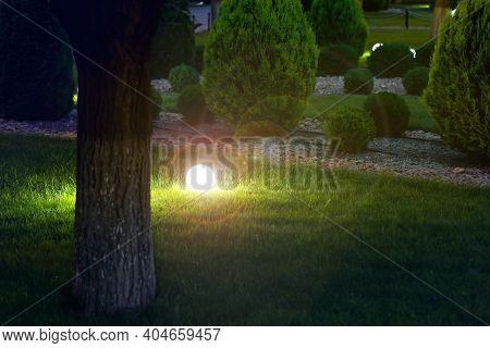 Ground Garden Lantern With Light Glare By Electric Lamp With A Ball Diffuser In The Green Grass In F