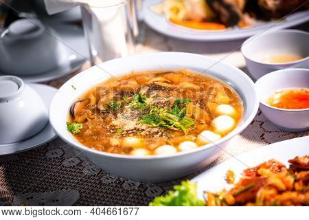 Chinese Style Soup Or Braised Fish Maw In Red Gravy With Eggs, Mushroom, And Bamboo Shoot In White B