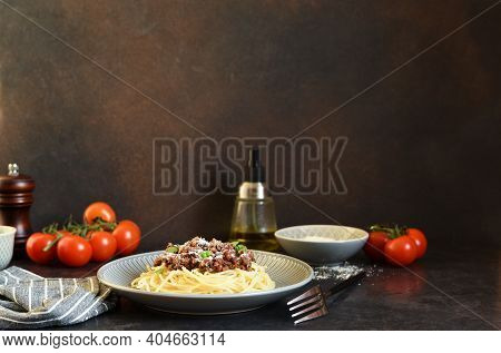 Spaghetti With Bolognese Sauce, Basil And Parmesan On A Dark Concrete Background.
