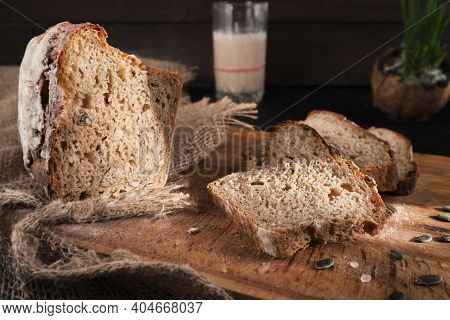 Fresh Homemade Leavened Bread In The Sun, Partially Sliced. Bread Is Located On A Wooden Surface. Ho