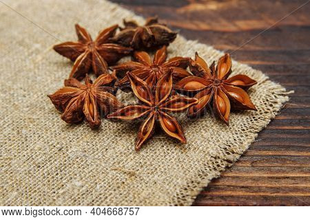 Dry Seasoning Anise On A Linen Napkin And On A Brown Wooden Background Close-up, The Concept Of Spic