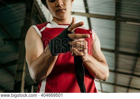 Portrait Of Boxer Fighter Applying Bondage Tape On Hands
