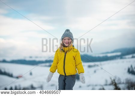 Funny Winter Kid Girl. Children Play With Snow Flakes
