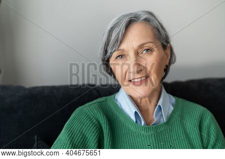 A Headshot Of A Charming Beaming Old Lady, Gray-haired Senior Mature Woman Sitting In The Living Roo