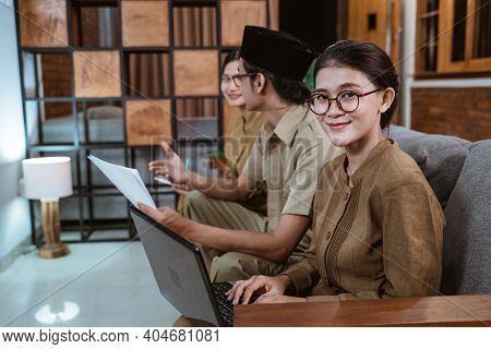 Female Teacher In Civil Servant Uniform Smiling Looking At The Camera While Using A Laptop Computer