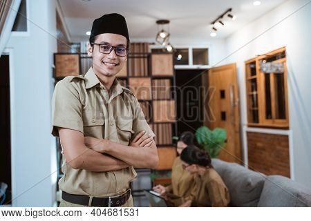 Male Teacher In Civil Servant Uniform Smiling With A Crossed Hand While Working With The Team From H