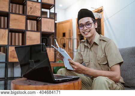 Male Teacher In Civil Servant Smile Looking At Camera When Working From Home Using Laptop Computer