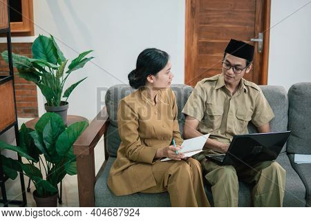 Woman And Man In Civilian Uniforms Using Laptop And Workbook While Sitting