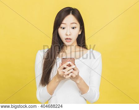 Shocked Young Woman Looking At Mobile Phone