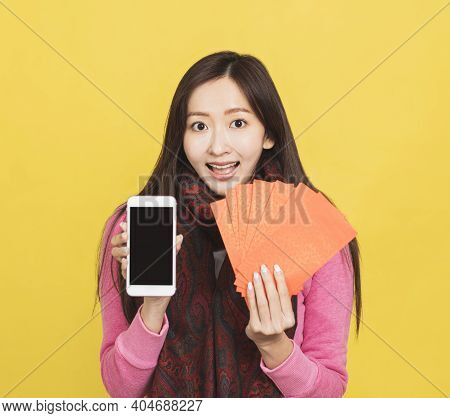 Asian Woman Showing Red Envelpoe And Mobile Phone Screen,  Celebrating Chinese New Year Concept