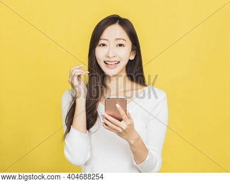Smiling Casual Young Woman Holding Smartphone Background