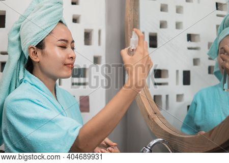 Asian Girl Wears A Towel While Spraying Facial Skin Moisturizer