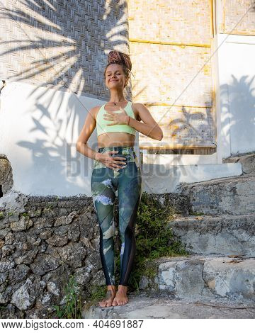Outdoor Yoga Practice. Young Woman Standing On The Stairs. Happy And Smile. Closed Eyes. Pranayama P