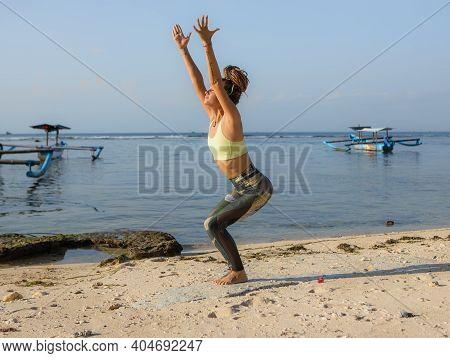 Caucasian Woman Practicing Utkatasana, Chair Pose. Low Squatting Asana In Hatha Yoga. Hands Raised U