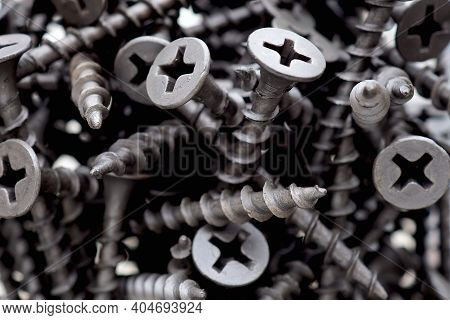 Lots Of Black Self-tapping Screws Close Up. A Bunch Of Hardware. Fasteners And Materials For Constru