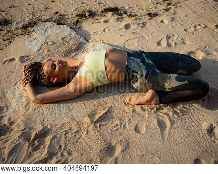 Yoga On The Beach. Beautiful Woman Lying On The Sand, Practicing Supta Virasana Reclining Hero Pose.