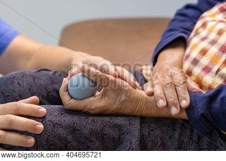 Elderly Woman Doing Rubber Ball For Exercise Fingers, Palm ,hand And Foot Muscle With Caregiver Take