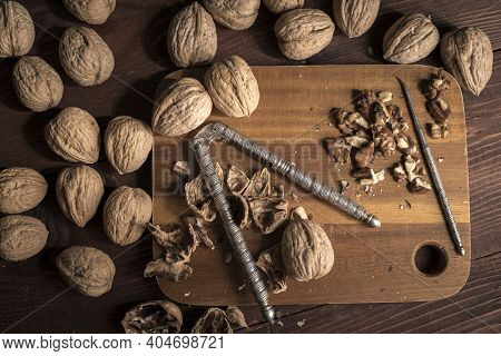 Overview Photo Of Whole Walnuts In Their Shell, Broken Shells, And Shelled Walnuts.