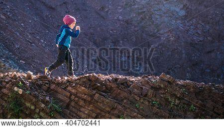 A Boy Runs Along A Mountain Path. A Child Walks Through The Forest. Active Kid Walks In The Park.