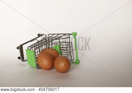 Trolley With Eggs Overturned On A White Background. The Mini Egg Cart Is Upside Down. Supermarket Tr