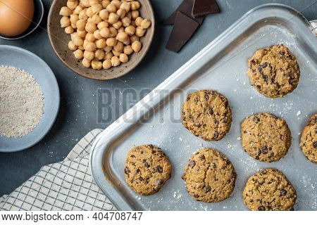 Horizontal composition of a baking tray with freshly baked chickpea cookies and dark chocolate chips