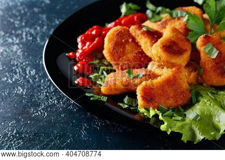 Fried Nuggets With Ketchup, Sprinkled With Chopped Parsley On A Black Plate.