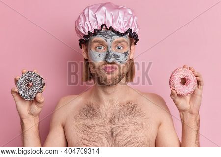 Photo Of Handsome Blue Eyed Guy With Thick Bristle Keeps Lips Folded Applies Moisturising Clay Mask