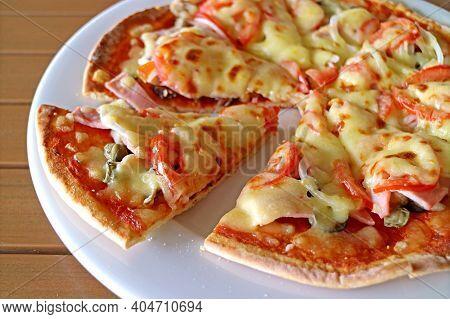 Delectable Crispy Cheesy Ham And Tomato Pizza On A White Plate