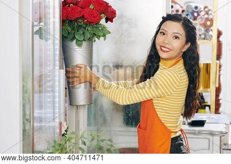 Atractive Smiling Asian Florist Taking Bucket Of Roses Out Of Floral Display