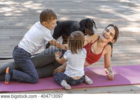 Young Beautiful Mother With Baby Son, Daughter And With Dog Exercising And Doing Yoga At Summer Park