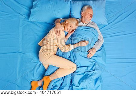 Senior Couple Sleep Peacefully Together In Bed Sleep And Enjoy Comfort. Pleased Blonde Middle Aged W