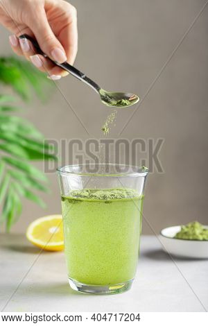 Woman Preparing Drink With Green Superfood Powder. Healthy Drink For Immunity Support. Vertical Imag