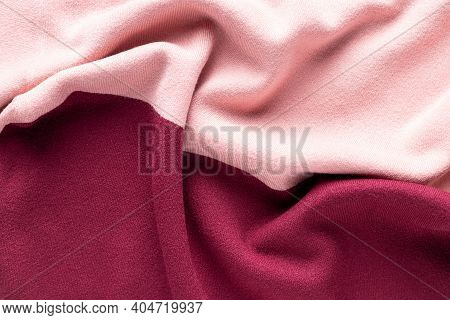 Pink And Burgundy Knitted Texture With Folds. Clothes Background. Fashion Colored Knitwear