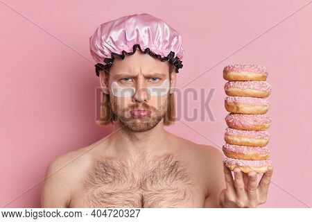 Unhappy Man With Gloomy Expression Stands Topless Indoor Holds Pile Of Sweet Doughnuts Applies Colla