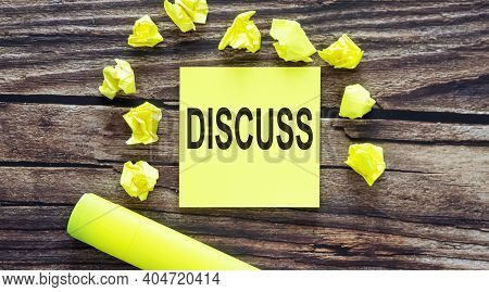 Notes About Discuss ,concept On Yellow Stickers On Wooden Background
