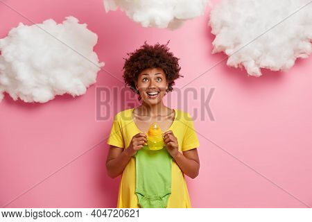 Glad Afro American Woman Holds Babies Clothes And Feeding Bottle Concentrated Above Positively Antic