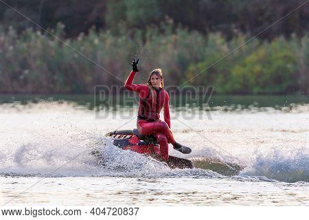 Krasnodar, Russia - October 25, 2020: Beautiful Sportsman Woman On Jet Ski Making Freestyle, Splashi