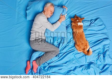 Man Dog Owner Of Old Age Sleeps Peacefully Together With Pet Poses In Bed Wears Pajama And Socks Lyi