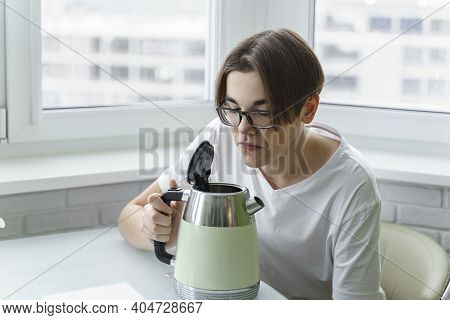 A Young Man In Glasses And A White T-shirt Smells Unpleasant From The Electric Kettle