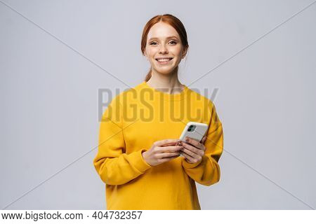 Happy Smiling Young Woman Holding Mobile Phone And Looking At Camera On Isolated White Background. P