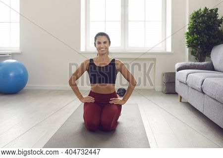 Portrait Of A Happy Athletic Woman Sitting On A Yoga Mat And Resting After Exercise.