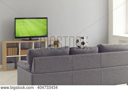 Modern Living-room With A Gray Couch And A Television Set With A Soccer Match On