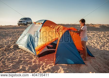 Beautiful Young Girl With Dark Hair Sets Up A Tent On The Beach. Auto Camping On A Sandy Deserted Be