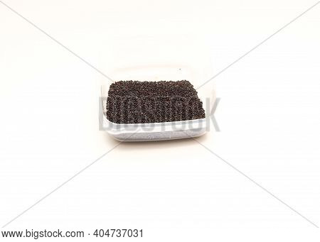 Small Plastic Container With Handful Of Bok Choy Chinese Cabbage Seeds Isolated On White Background